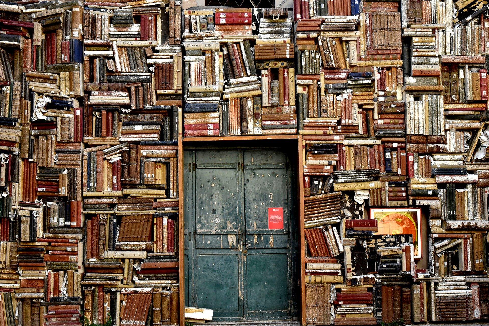 Pared repleta de libros y con una puerta cerrada en el medio