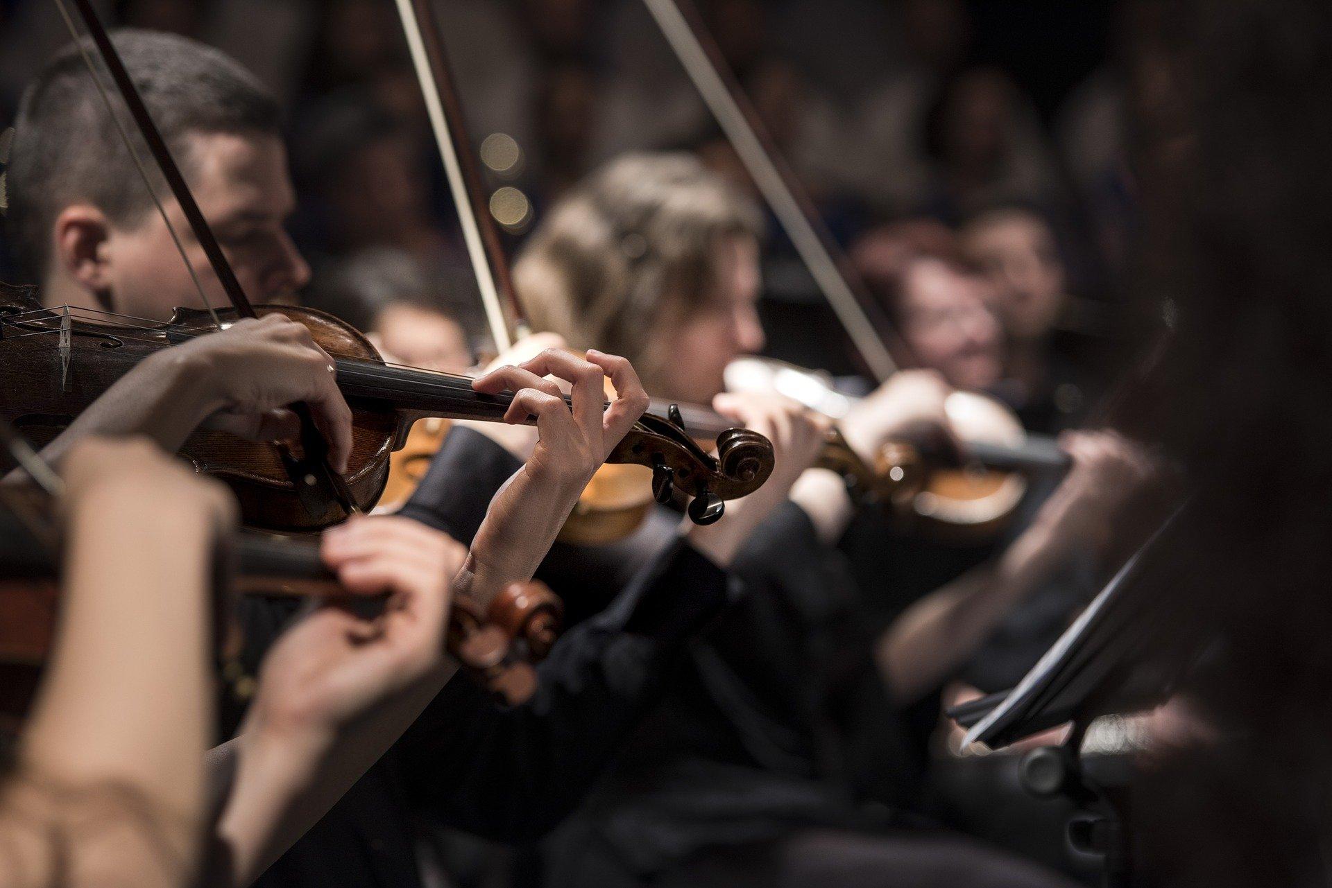 Primer plano de violinistas tocando en una orquesta
